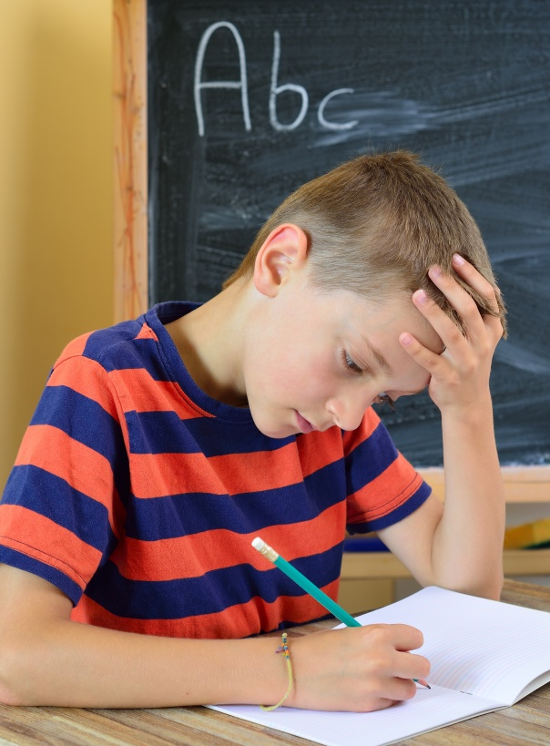21453265 - young boy tries to do his homework  the problem with learning